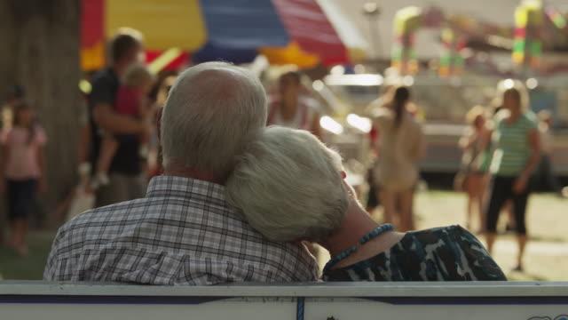 Medium shot of senior couple sitting on bench at carnival / American Fork, Utah, United States