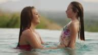 Medium shot of sisters playing in infinity pool / Cedar Hills, Utah, United States