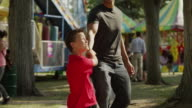Medium shot of son dragging father toward amusement park ride / American Fork, Utah, United States