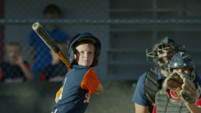 Medium shot of surprised batter hitting baseball and running / American Fork, Utah, United States