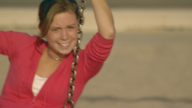 Medium shot of teen girl on a swing