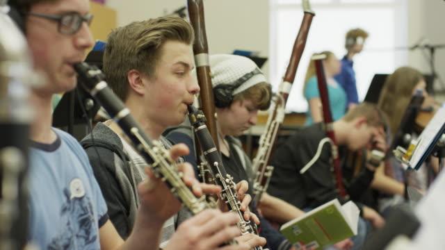 Medium shot of teenage boys in orchestra practice / American Fork, Utah, United States
