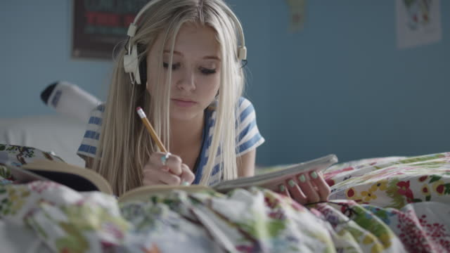 What are your opinions on listening to music while doing homework     Girl         listening music and doing homework on bed   Stock Photo