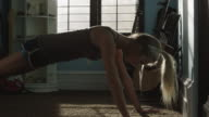 Medium shot of teenage girl doing push-ups in bedroom / Sandy, Utah, United States