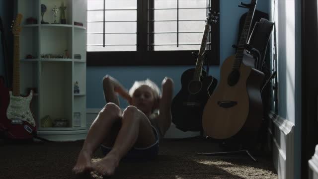 Medium shot of teenage girl doing sit-ups in bedroom / Sandy, Utah, United States