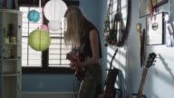 Medium shot of teenage girl playing electric guitar / Sandy, Utah, United States