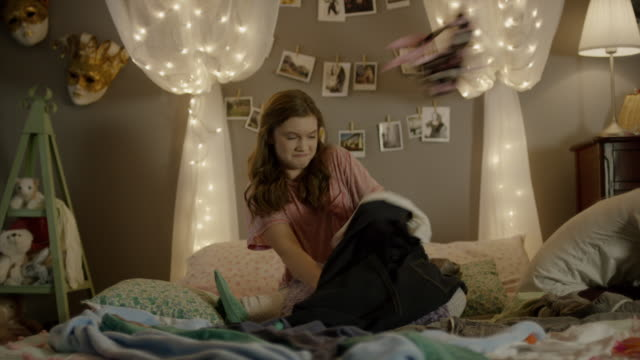 'Medium shot of teenage girl searching for clothing in bedroom / Cedar Hills, Utah, United States'