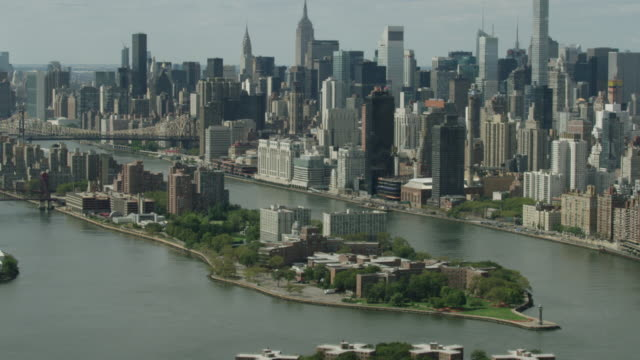 Medium shot of the Roosevelt Island with the Queensboro Bridge and Manhattan buildings in the background