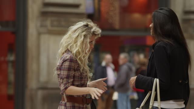 Medium shot of two women arguing in shopping mall / Milan, Italy
