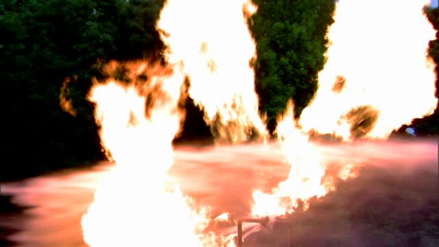 Medium shot of water being sprayed onto a fire from a broken liquid propane pipe.