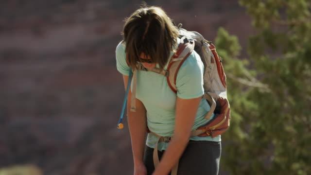 Medium shot of woman hiker playing with dog / Moab, Utah, United States