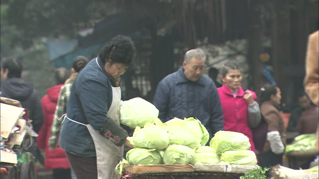 Medium shot of woman selling vegetables (cabbages)