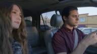 Medium shot of woman taking cell phone from man driving car / Provo, Utah, United States