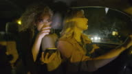 Medium shot of women in car using cell phone for navigation / Provo, Utah, United States