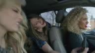 Medium shot of women singing and posing for cell phone selfie in car / Provo, Utah, United States