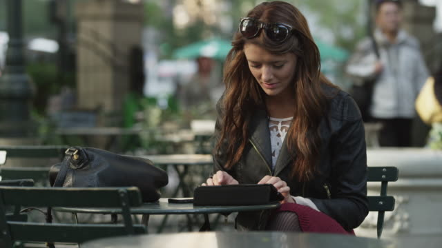 Medium shot of young woman using digital tablet at sidewalk cafe / New York City, New York, United States