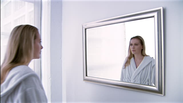 Medium shot of young woman walking towards a mirror and watching her reflection transform into an older woman.