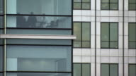 Medium shot office building exterior with people in conference room/ London