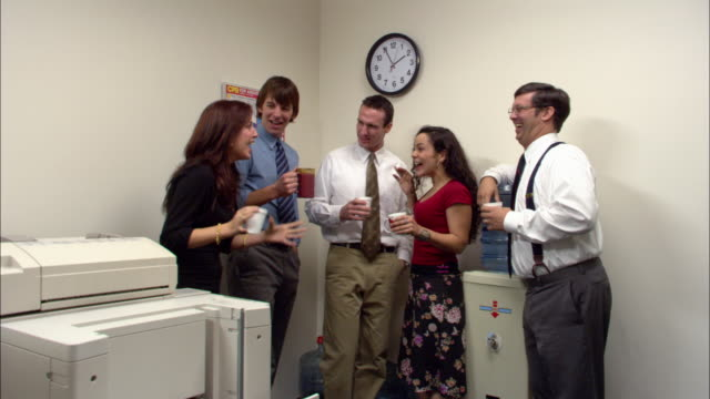 Medium shot office employees gossiping by water cooler / boss entering / employees quickly leaving / low angle