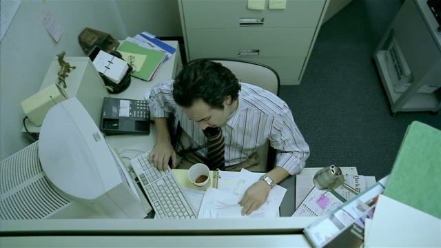 Medium shot overhead view of man working and talking on phone in cubicle / spilling coffee on pants