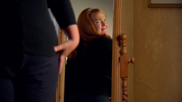 Medium shot overweight woman looking at herself in mirror unhappily