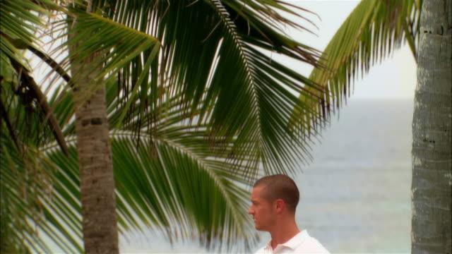 Medium shot palm trees in front of sea/ tilt down portrait hotel worker holding breakfast tray/ Harbour Island, Bahamas