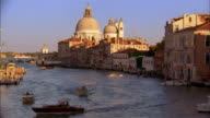 Medium shot pan across canal w/domed building in background / Venice, Italy