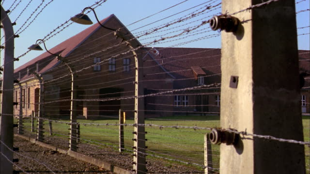 Medium shot pan barbed wire fence and electric yard at Auschwitz Concentration Camp / Poland