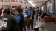 Medium shot pan behind ticket counter with agents helping customers / Hartsfield Airport, Atlanta