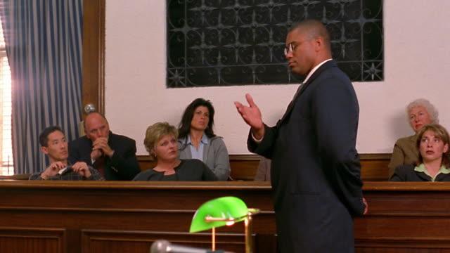 Medium shot pan Black lawyer talking to jury / paintiff in foreground
