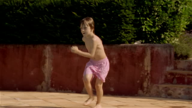 Medium shot pan boy running and doing 'cannonball' into swimming pool/ Saint-Ferme, France