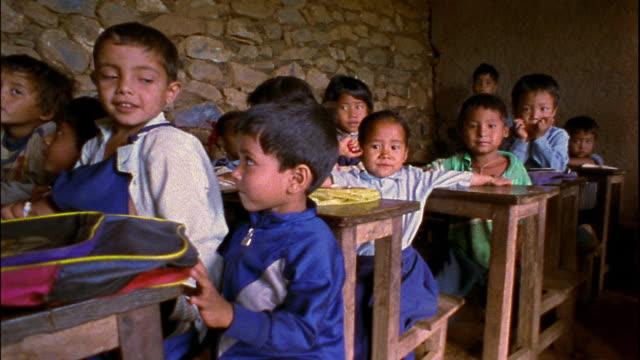 Medium shot pan children in small classroom within stone building / Nepal