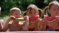 Medium shot pan children in swimsuits eating slices of watermelon / New York