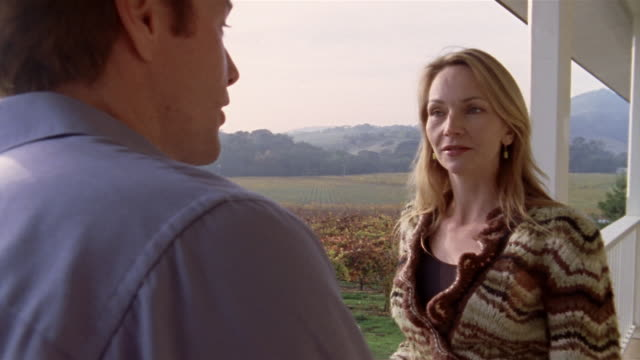 Medium shot pan couple talking on porch at vineyard/ Napa Valley, California