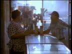 Medium shot pan customer talking to hardware store clerk over counter