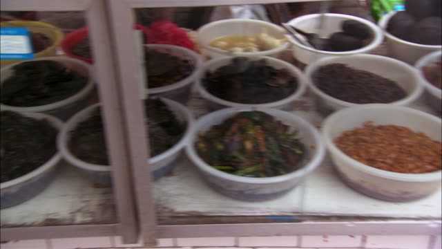 Medium shot pan dishes of food and shoppers at market / Taishan
