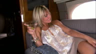 Medium shot pan Diva laughing, reclining and holding martini on private airplane