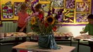 Medium shot pan elementary school children painting flower arrangement in art class/ London