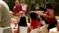 Medium shot pan family attending barbecue in backyard