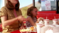 Medium shot pan family eating french fries and laughing outside fast food restaurant