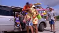 Medium shot pan family exiting minivan / man opening trunk / family unloading water toys