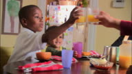 Medium shot pan family making toast with orange juice at breakfast table