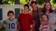 Medium shot pan family posing by tire swing in front yard of suburban house