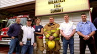 Medium shot pan firefighters standing in front of fire station and smiling at CAM w/fire trucks+ sign in background