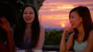 Medium shot pan four young women sitting at rooftop table at sunset and talking / New York City