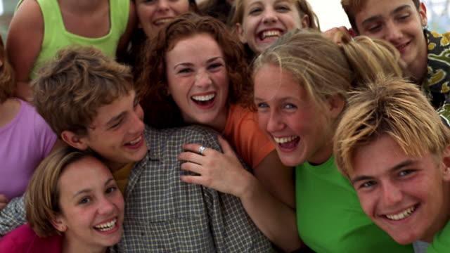 Medium shot pan group of teens smiling and laughing at camera outdoors