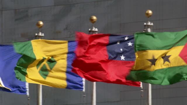 Medium shot pan international flags waving in wind at United Nations / New York City