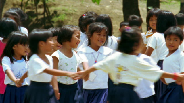 Medium shot pan large group of elementary schoolgirls holding hands and turning in schoolyard / Philippines