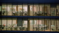 Medium shot pan looking into glass office building at night