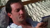 Medium shot pan man lying on hammock and reading